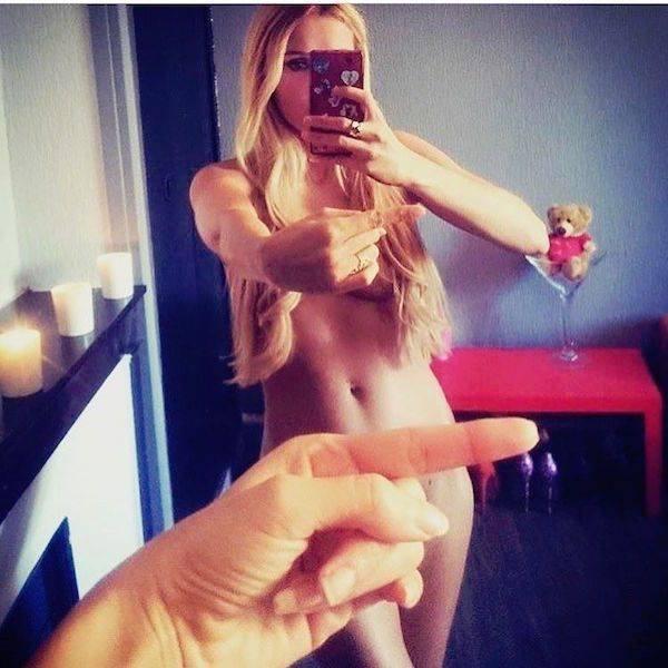 Девушки в зеркале, прикрытые с помощью одного пальца
