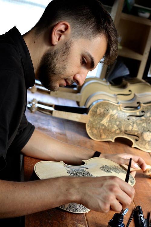 Художник вручную расписывает скрипки и виолончели