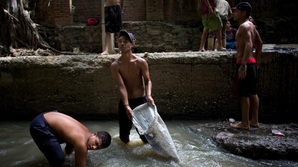 Молодые венесуэльцы ищут металл в реке