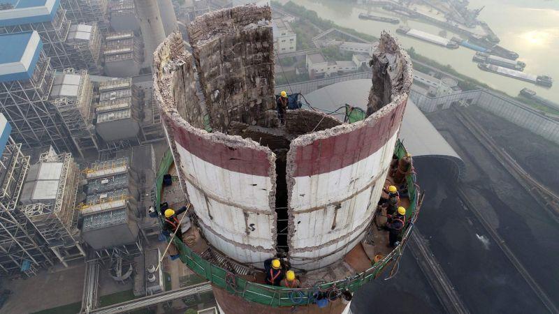 Рабочие вручную разбирают дымовую трубу высотой 180 метров