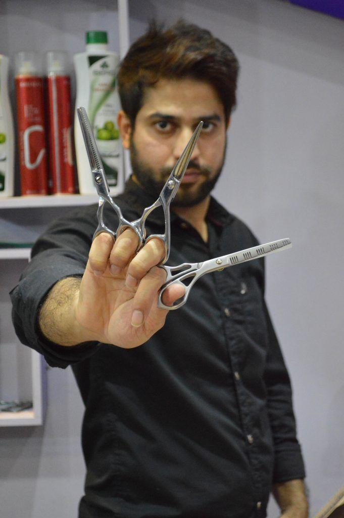 Парикмахер стрижет клиентов одновременно 27 парами ножниц