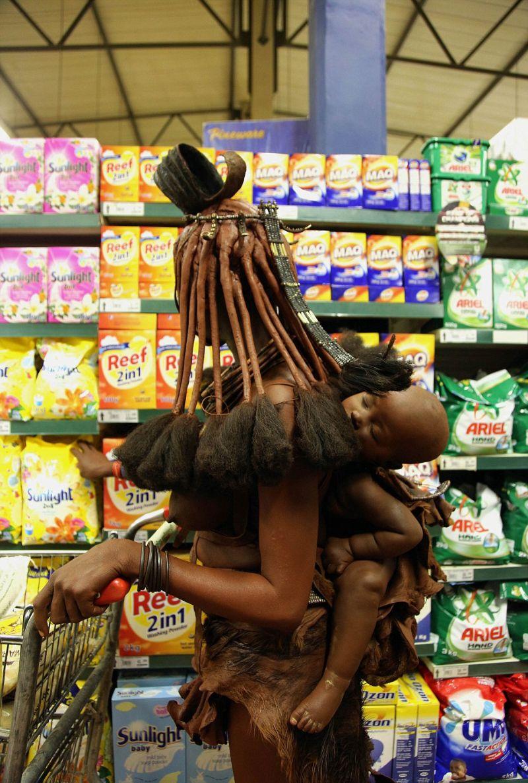 Женщина народа химба в традиционном наряде делает покупки в супермаркете