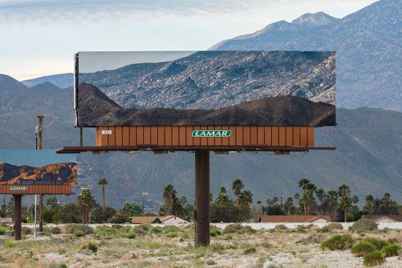 Художник заклеивает билборды пейзажами, которые те перекрывают