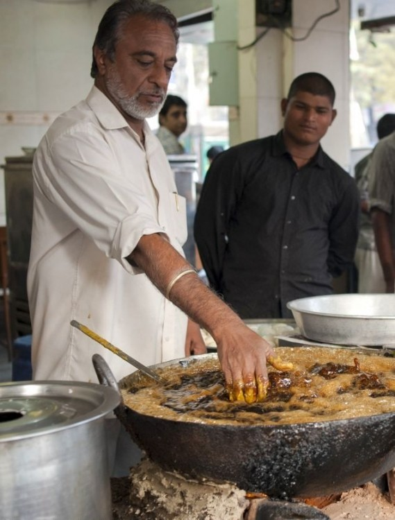 Индийский повар жарит рыбу в кипящем масле голыми руками