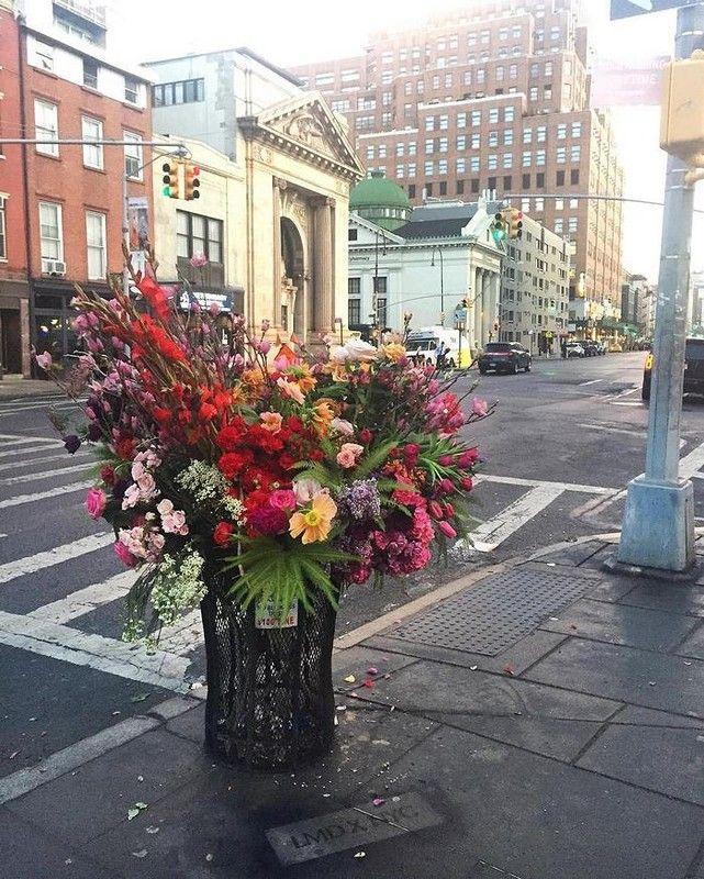 Дизайнер украшает урны цветами, использованными на мероприятиях