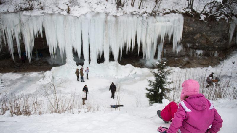 Скала с замерзшим водопадом привлекает толпы туристов