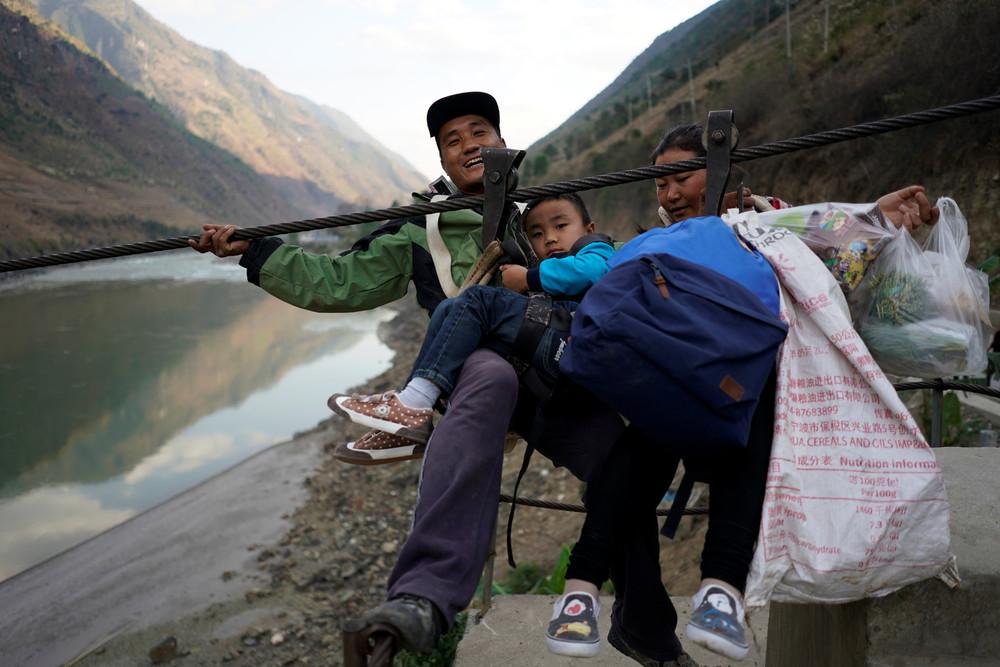 Жители китайской деревни используют стальной канат для переправы через реку