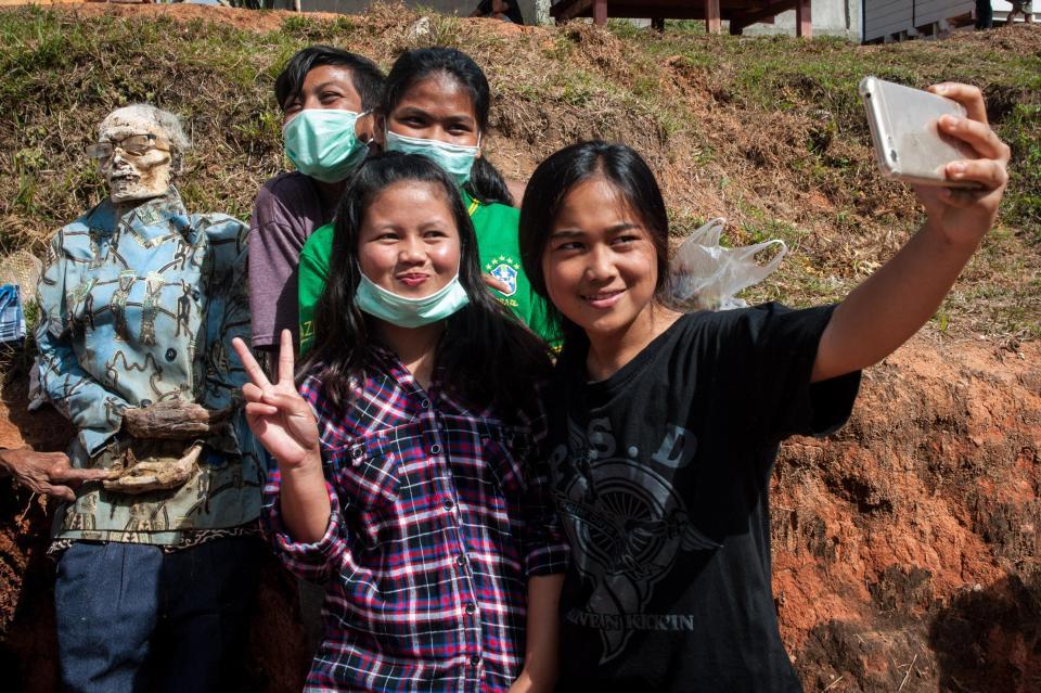 Туристы позируют на индонезийском фестивале мертвых родных