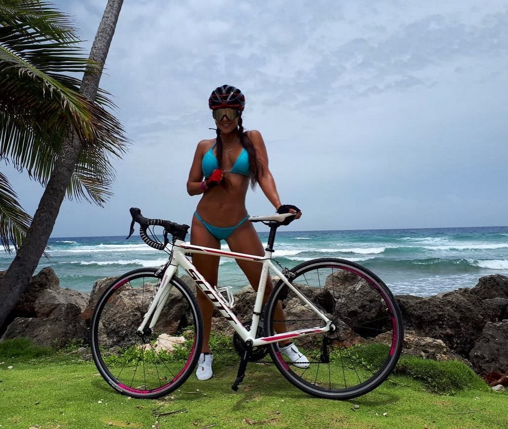 Mature woman riding bicycle on path by beach smiling high