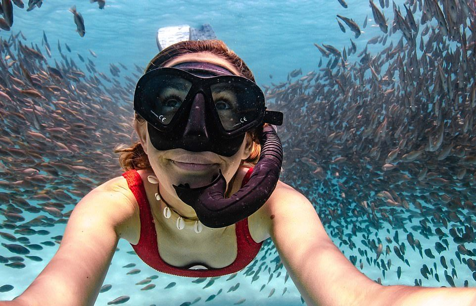 Фридайверы плывут через косяк рыб