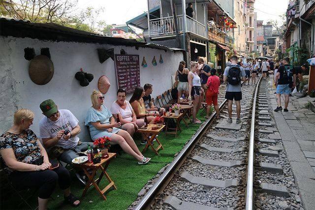 Кафе возле железной дороги, посетители которого отдыхают на рельсах