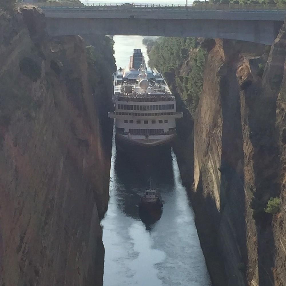 Большой круизный корабль протискивается по узкому каналу в Греции