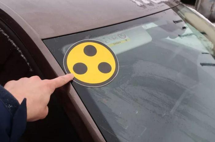 Что означает желтый круг с черными точками на автомобиле