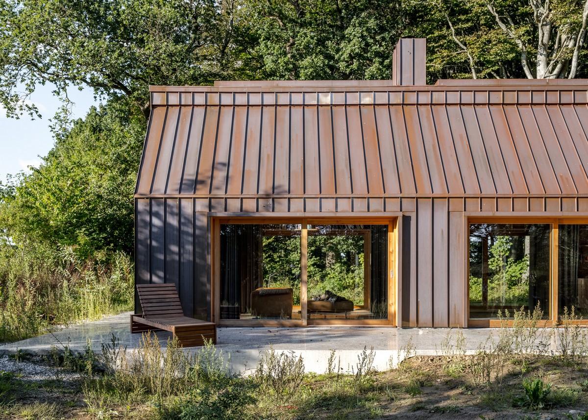 Медный дом творческого человека в лесу у озера в Дании
